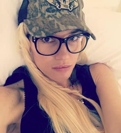 Gwen Stefani wearing black rimmed glasses and mystery hat