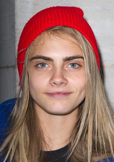 Cara Delevingne wearing a red beanie without makeup on