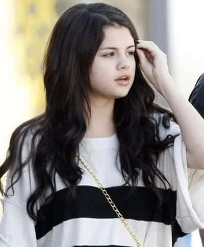 Selena Gomez fixing her hair