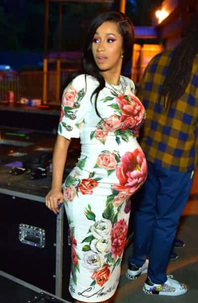 Cardi B in a vintage flower piece showing off her baby bump
