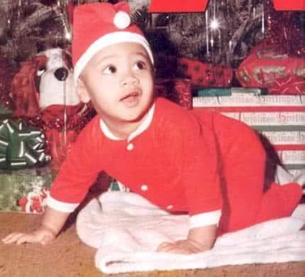 Baby Dwayne Johnson dressed up as Santa crawling on the floor