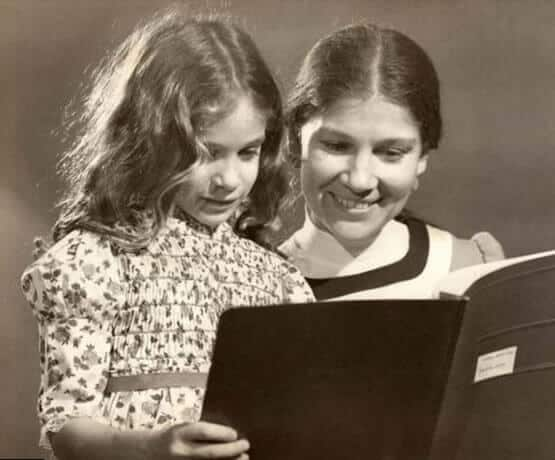 Young Sarah reading with her mom