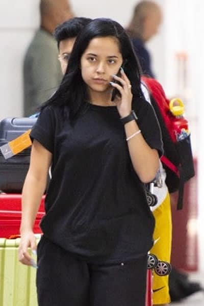 Becky G talking on the phone through the airport