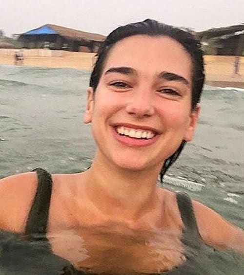 Dua Lipa swimming at the beach looking very happy