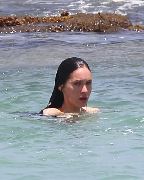Megan Fox swimming near the rocks on the beach